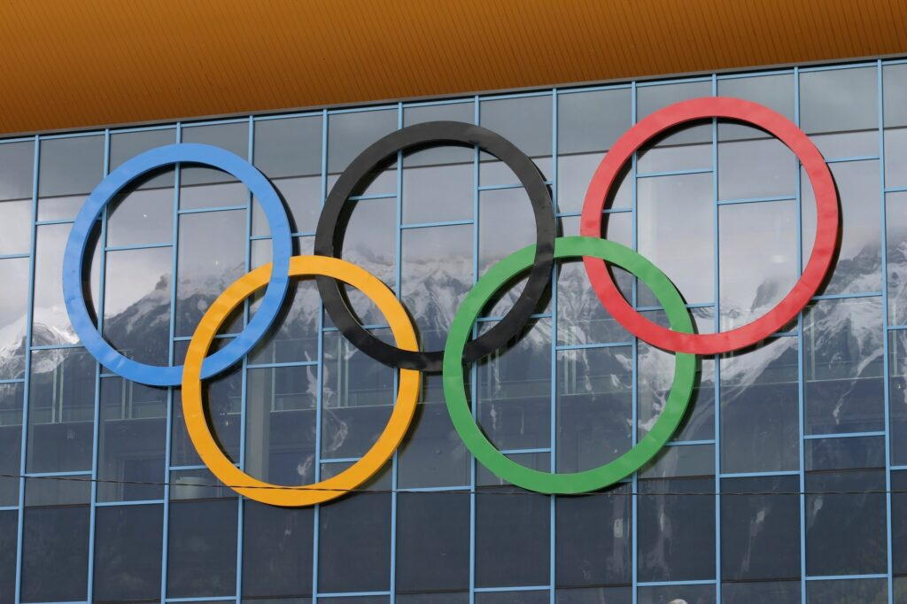 Symbol olimpiady (pięć kół olimpijskich) na tle obiektu sportowego. W szybach obiektu widać odbicie wysokich gór.