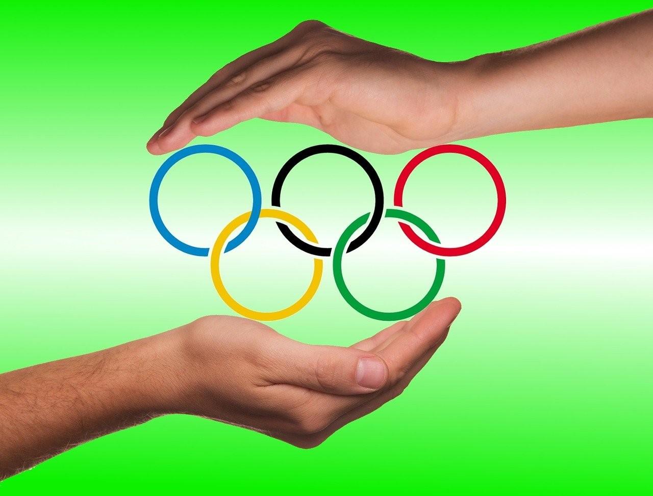 Grafika na zielonym tle. Logo Olimpijskie (pięć olimpijskich kół) w otoczeniu ludzkich dłoni wspierających ruch olimpijski